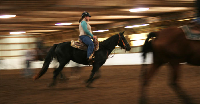 A female rides a horse galloping indoors at Morrisville State College.