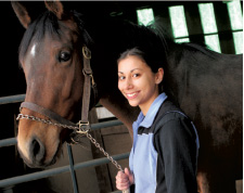 Cobleskill student stands with horse inside barn.