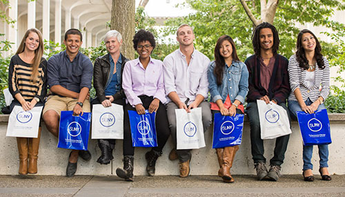 SUNY sitting students on wall with SUNY bags in front of them.