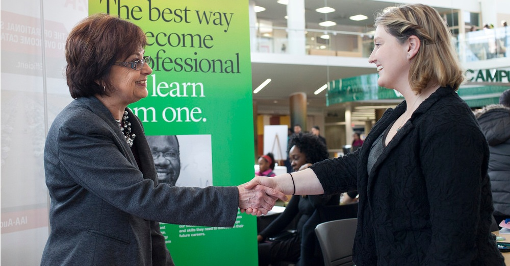 2 Females shaking hands at a job fair.