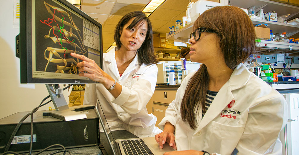 Two asian female researchers conducting TB research at StonyBrook.