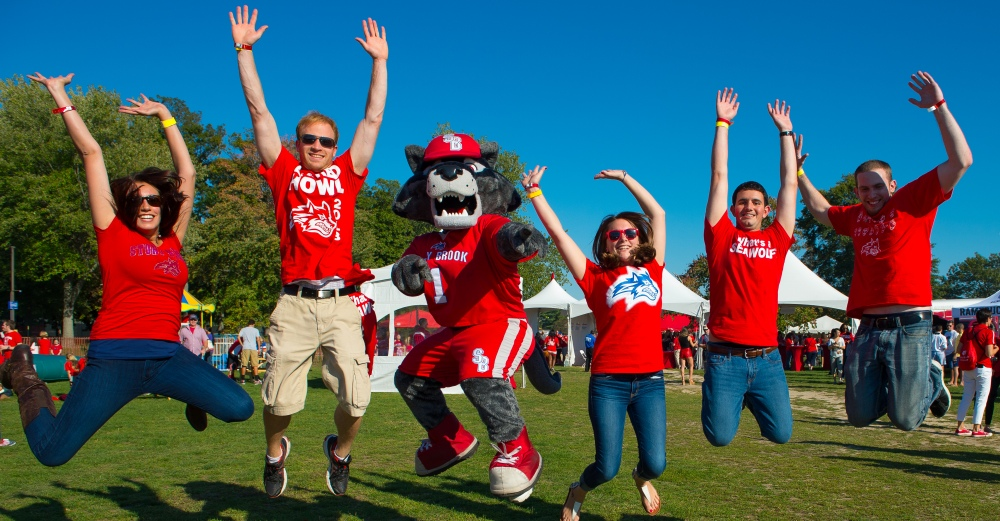 Students at Stony Brook University jump and cheer with mascot Wolfie at the campus Wolfstock event at 2014 Homecoming.