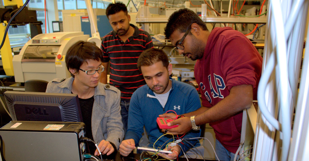 Workers at Advanced Materials Analytics of Binghamton University look over electronics.
