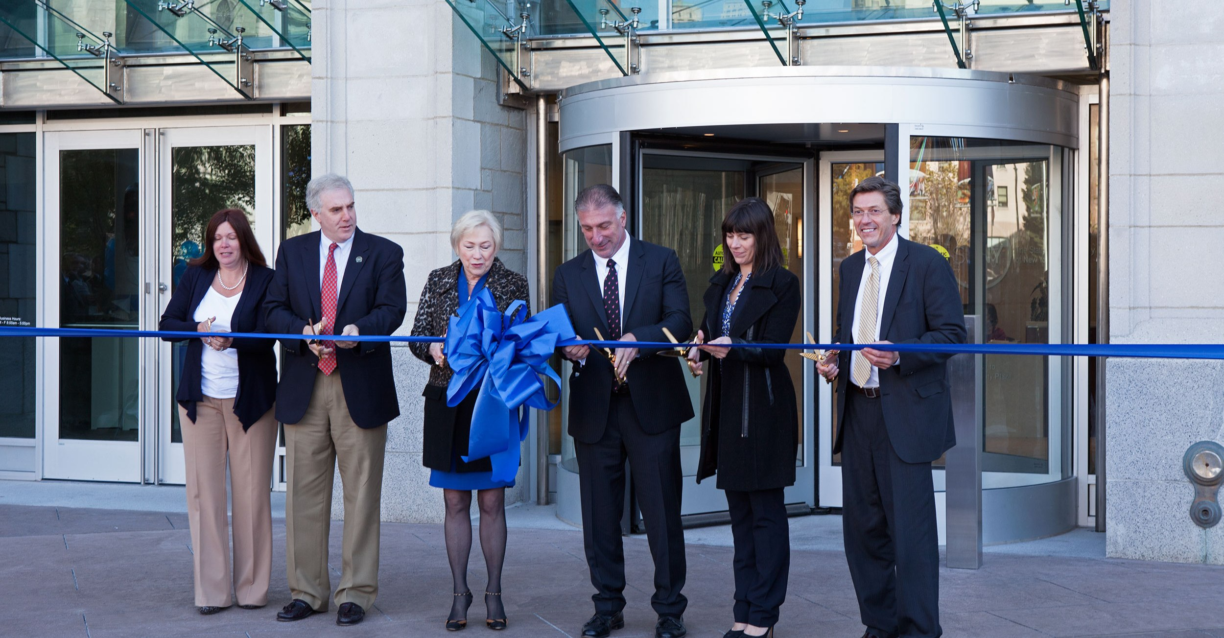 Chancellor Zimpher and city of Albany representatives prepare to cut the ribbon at SUNY System Administration renovation reopening.