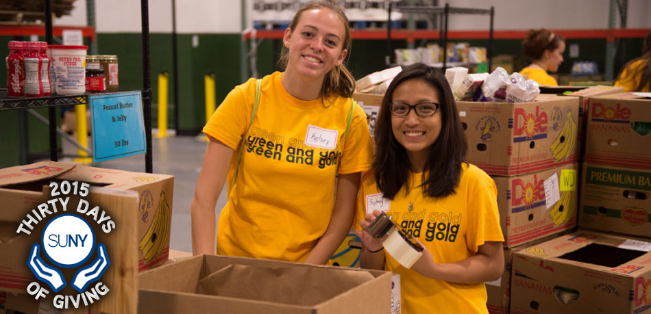 2 female Brockport students pack boxes of donations during Saturday of Service