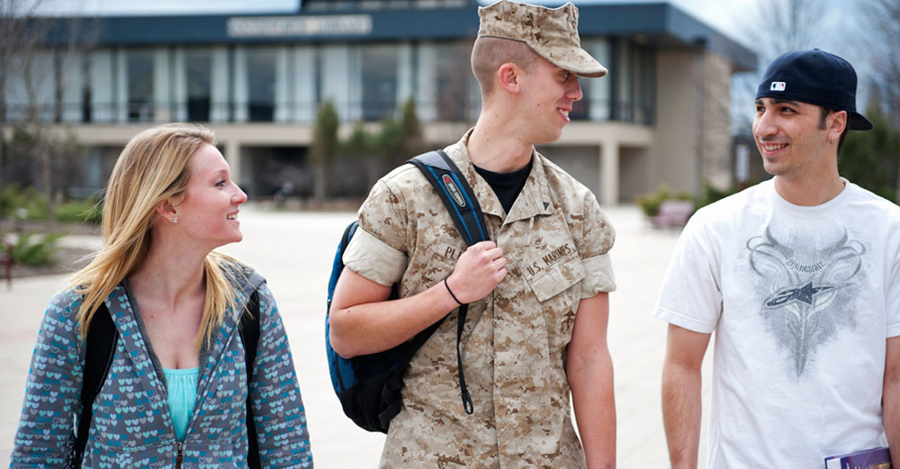 One student in military uniform and two students in casual clothes walk on college campus.