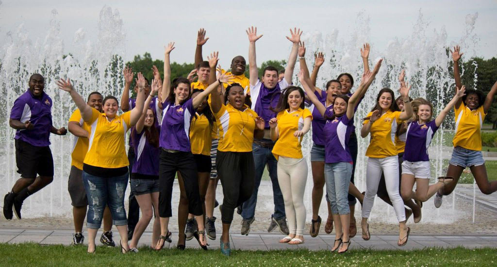 UAlbany students jump and cheer in front of school fountain