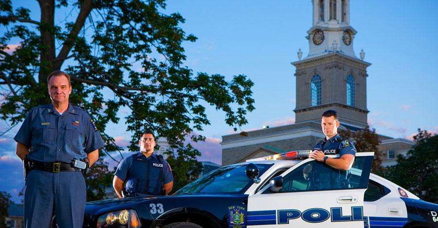 University at Buffalo police officers near squad car.