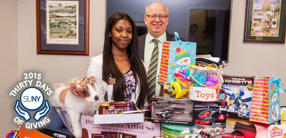 Canton Student Government Association Budget Director Fatizjah Burnett helps SUNY Canton President Zvi Szafran with nearly 100 gifts collected through the college's Giving Tree.
