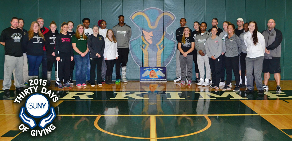 Herkimer County Community College students stand against wall for picture in gym.