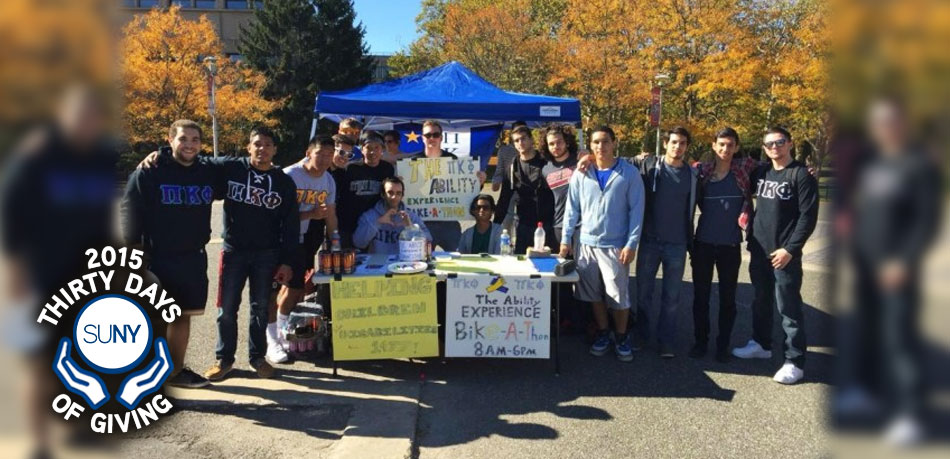 Members of a new fraternity at Stony Brook University, Pi Kappa Phi, at a canopy tent and table helping people with disabilities.