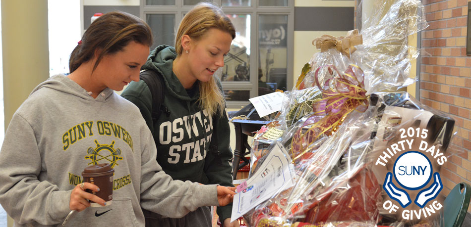 2 female Oswego students look at gift baskets on display.