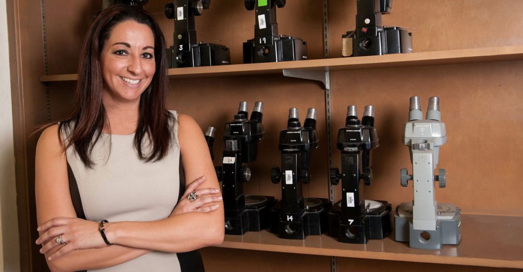 Michelle Miranda, associate professor at Farmingdale State College. stand in front of shelf of microscopes