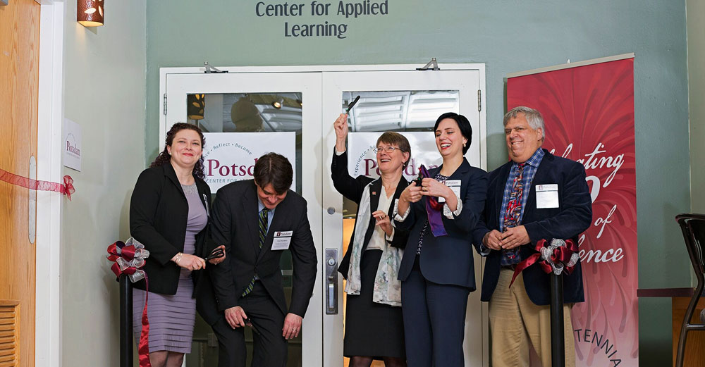The ribbon is cut at SUNY Postdam with campus leaders and SUNY System Admin staff
