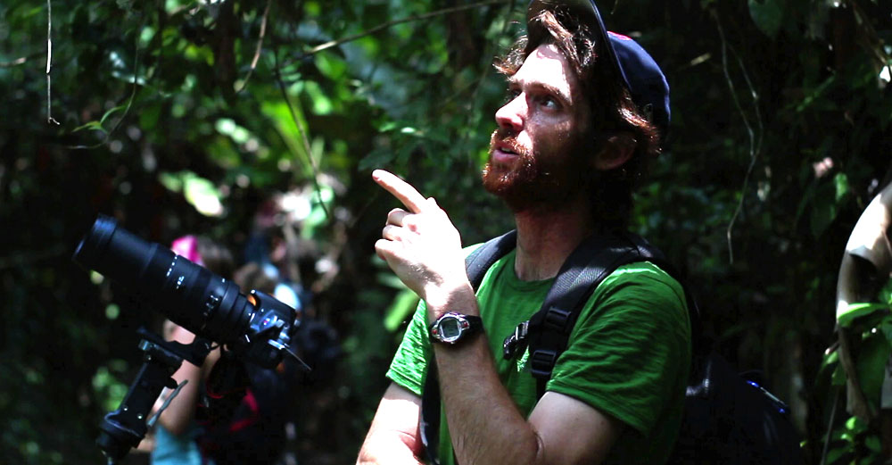 Paul Stoutenburgh, ESF alum, stands in the forest behind video camera.