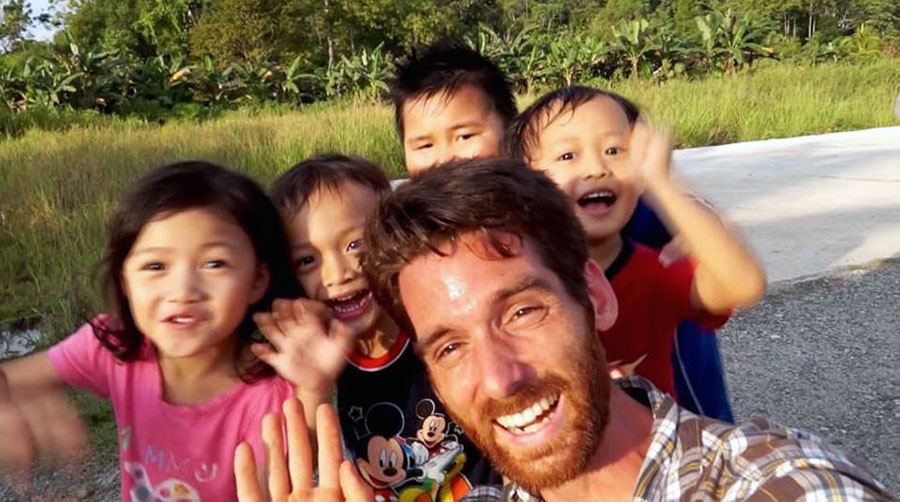 Paul Stoutenburgh in Malaysia with children while filming for the Borneo Project.