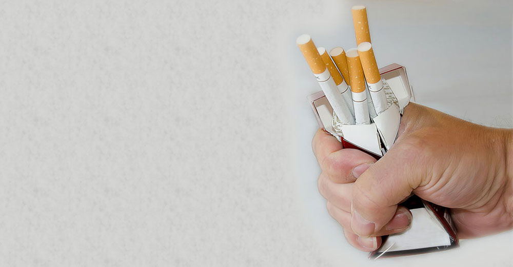 hand squeezing pack of cigarettes