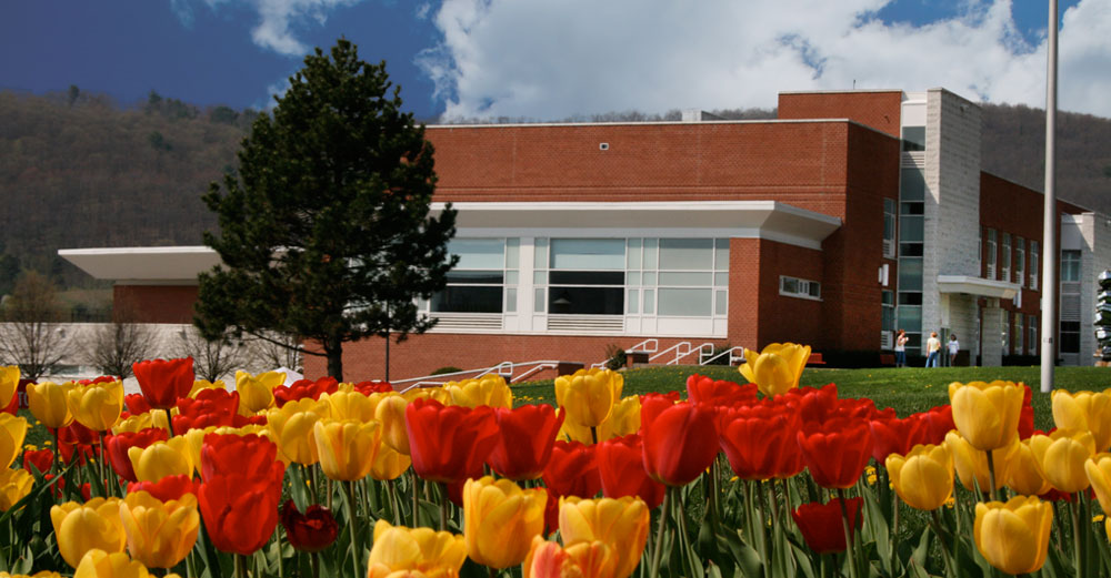 Broome Community College building behind tulips.