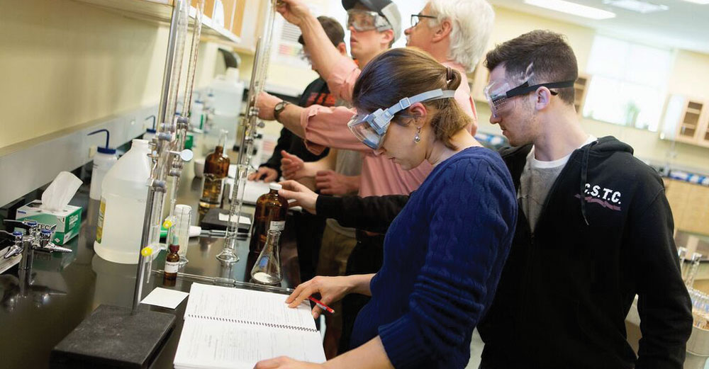 Adirondack Community College students wearing goggles in science lab.
