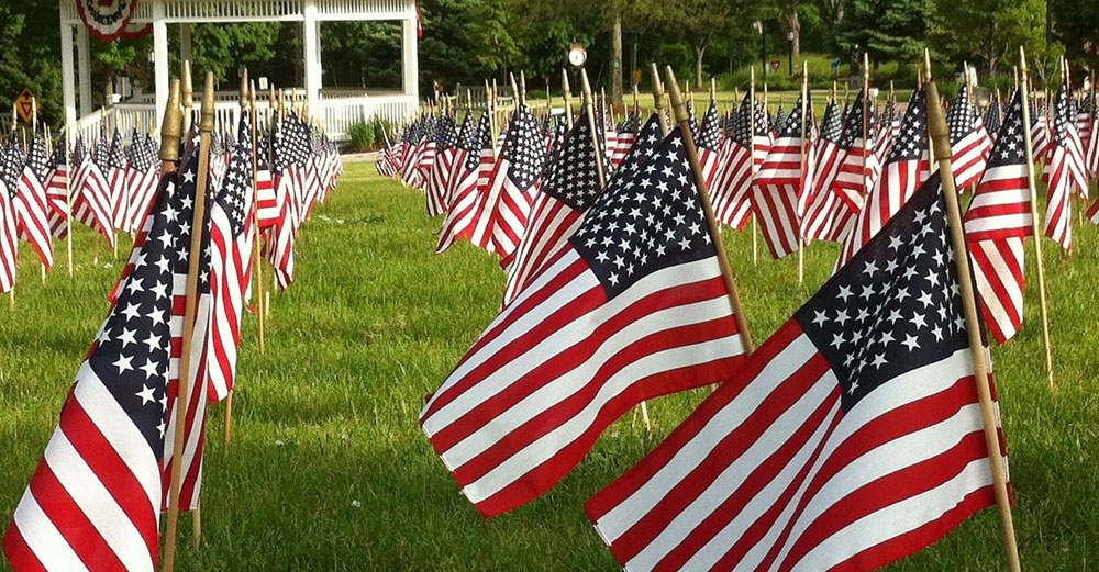 American flags in rows in the grass in front of gazebo.