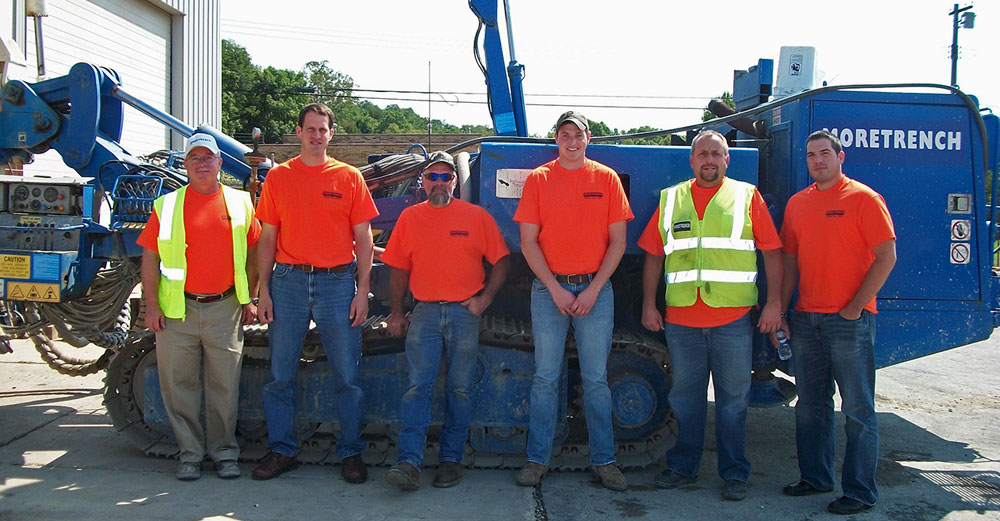 Farmingdale State College alum Arthur Corwin stands with his construciton crew outside in front of excavator.