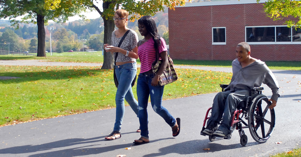 Students at Mohawk Valley Community College walk outside with student in wheelchair.