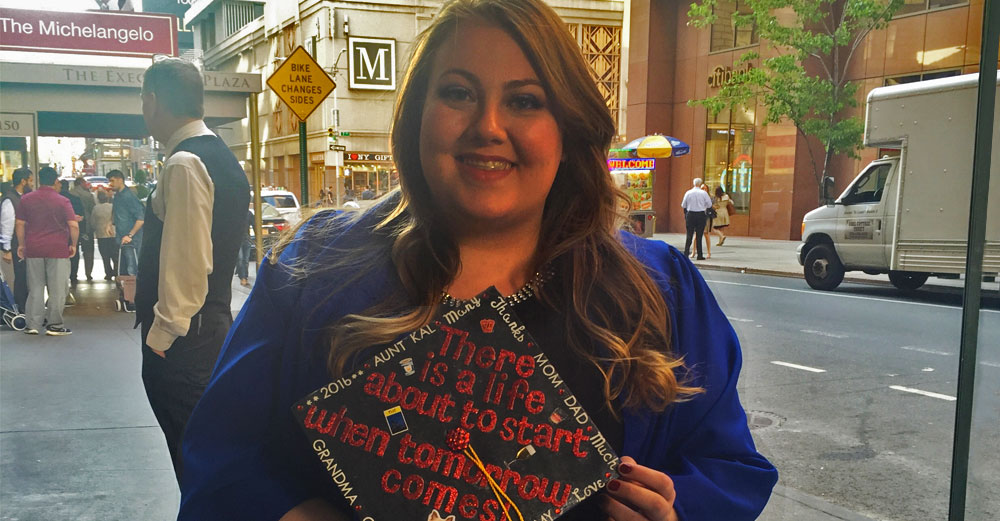 Heather Card, FIT alum via Open SUNY, stands in Manhattan street in her hraduation cap and gown.