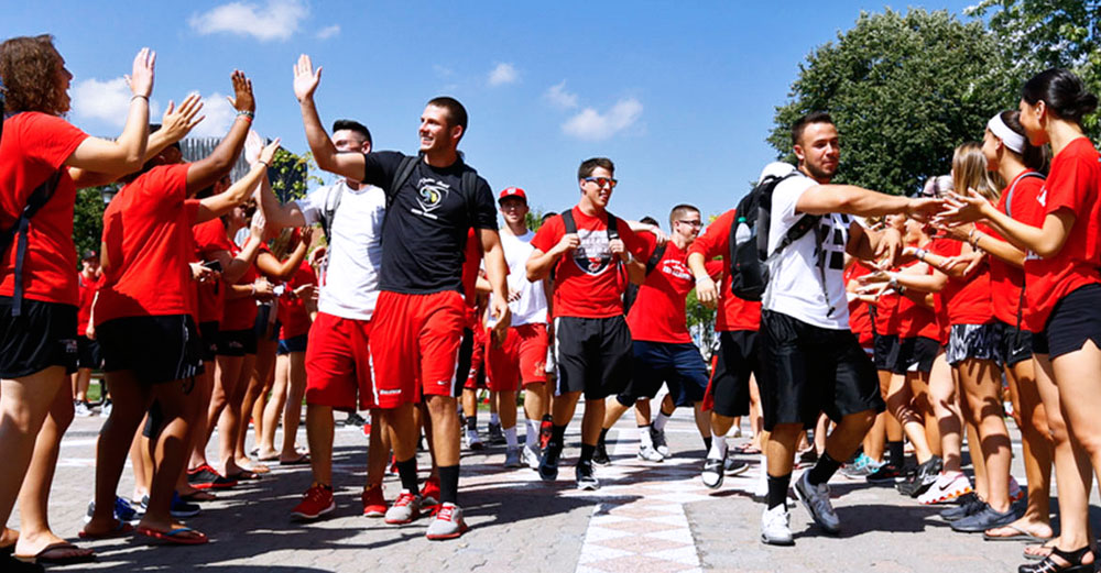 Students walking through high-five line on Oneonta Red Day