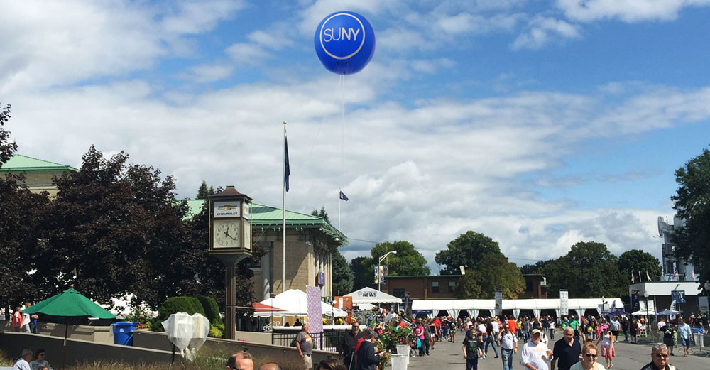 A giant blue SUNY balloon floats above attendees at the 2015 New York State Fair