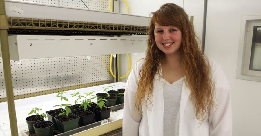 Cobleskill student Clara Richardson in lab coat in front of plants on table under light.