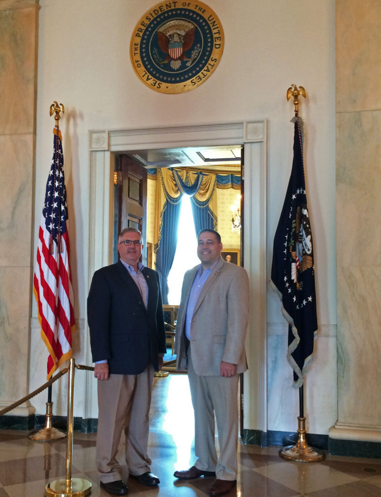 SUNY University Police Commissioner Paul Berger with Deputy Commissioner Michael Bailey stand in front of a doorway at the White House with the presidential seal above them.