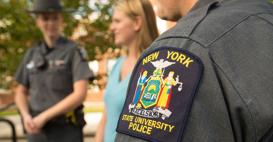 A SUNY Police badge on an officer's sleeve with a student behind him.