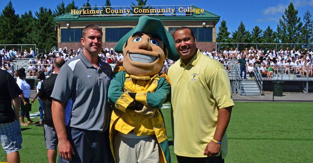 Dartray Belk with mascot and football coach at Herkimer Community College football field.