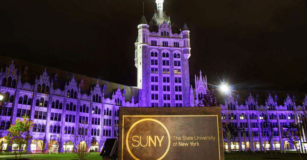 SUNY Plaza at night shining in purple light with SUNY sign in front.