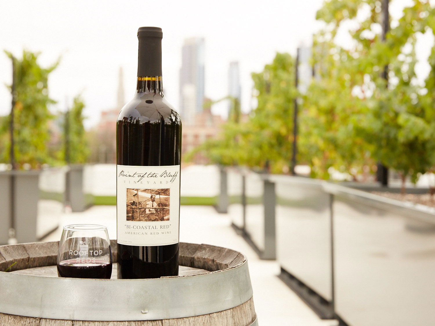 Bottle of red wine on top of a barrel at the Rooftop Reds location in Brooklyn.