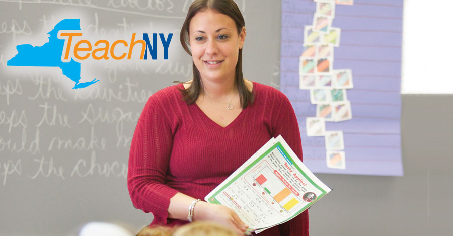 Female teacher stands in front of chalkboard with paper in hand.