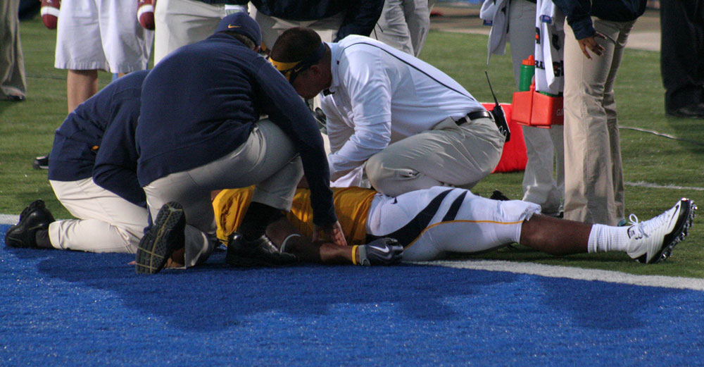 Football player down on the field with medical staff looking him over.