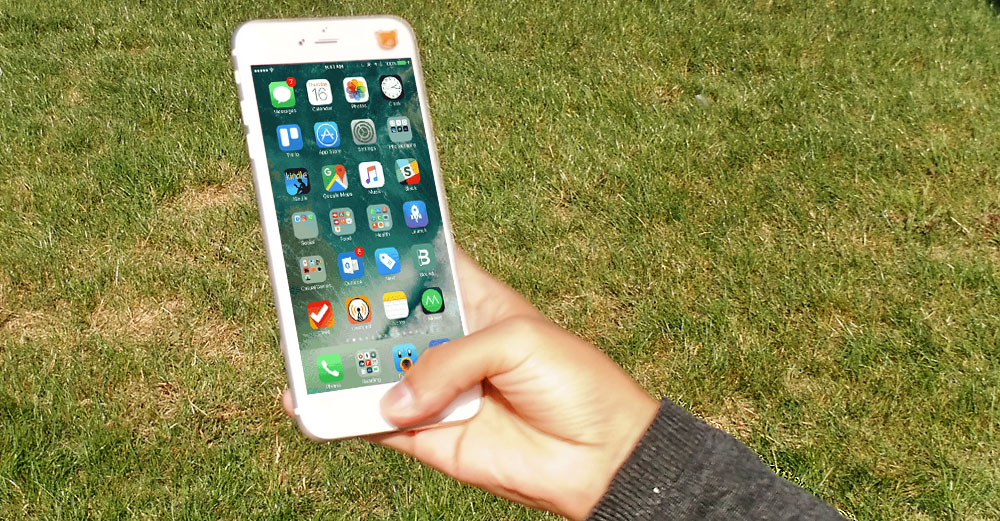 iPhone with ios10 held in hand outside.