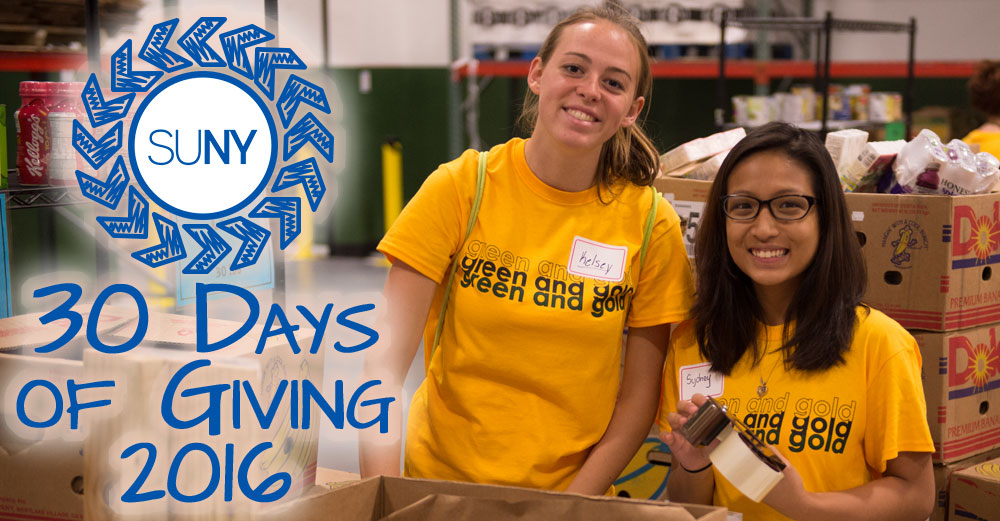 2 female students in front of boxes during a food drive. SUNY 2016 30 Days of Giving