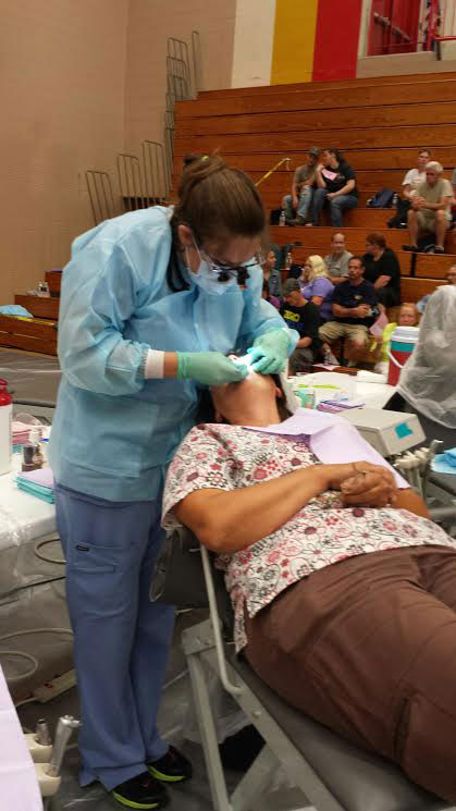 Farmingdale State student Kaitlyn Rostron gives a dental checkup to a patient in a gym.