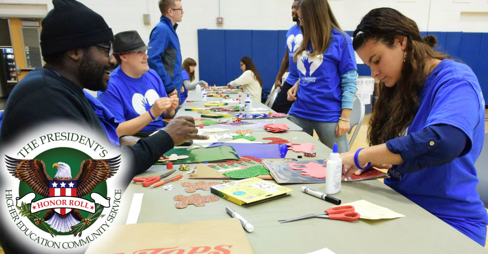 Students at Onondaga Community College design crafts at a table in the gym.