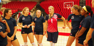 Lora Webster talks to the Stony Brook womens volleyball team on the court.