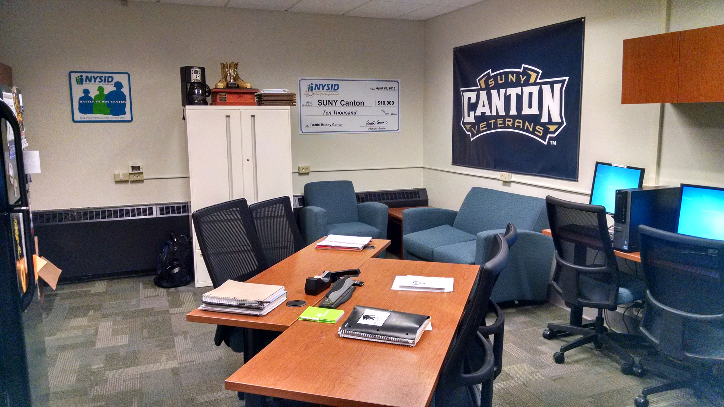 Interior of the SUNY Canton Battle Buddy Center, with couches, computers, workspaces, lockers.