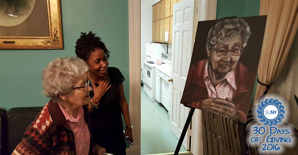 Cammie Jones, Dutchess Community College Service Learning Coordinator, looks at a painting in a senior center house with an elderly woman.