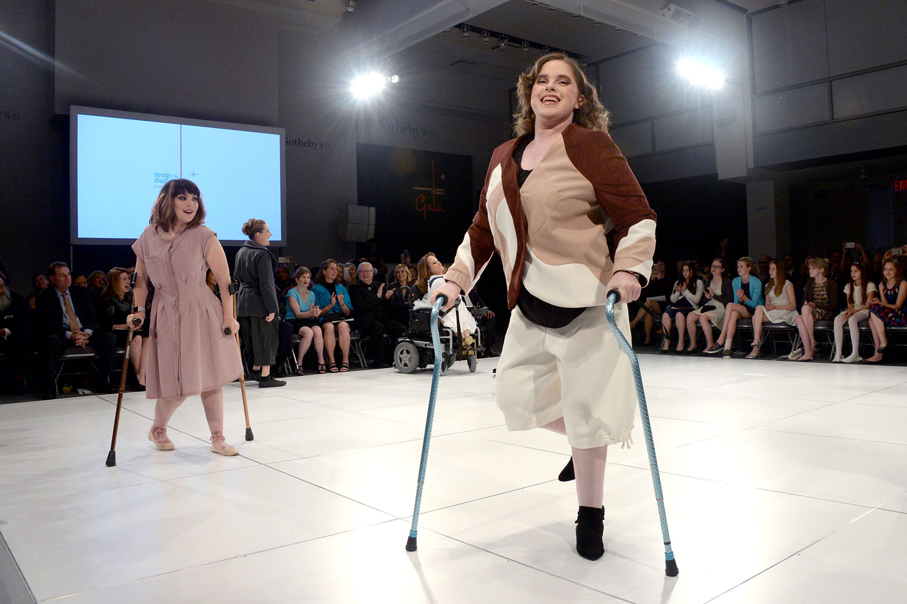 Disabled women on crutches on runway at FIT fashion show.