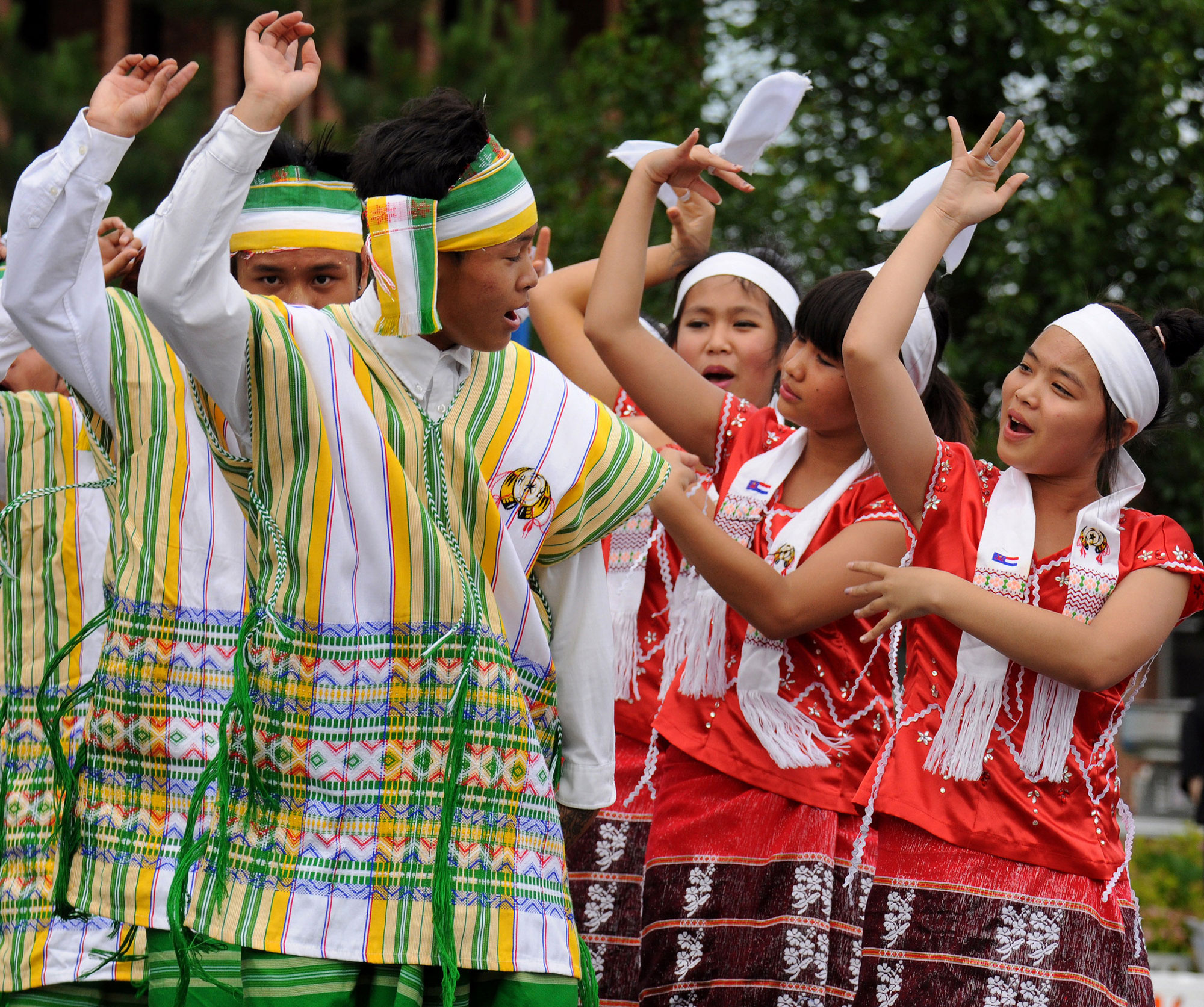 Refugee dancers outside in traditional outfits.