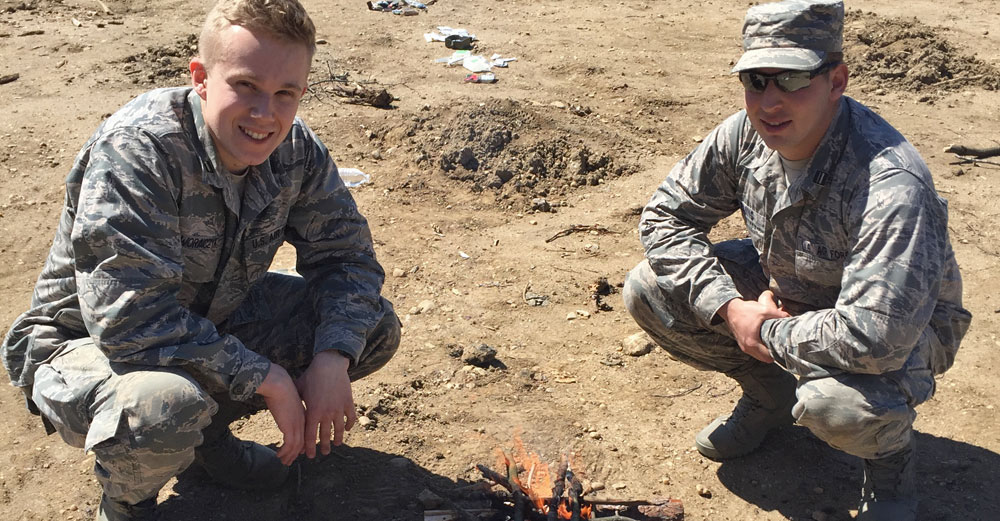 2 ROTC students from Farmingdale State College in uniform crouching down near self-made fire.