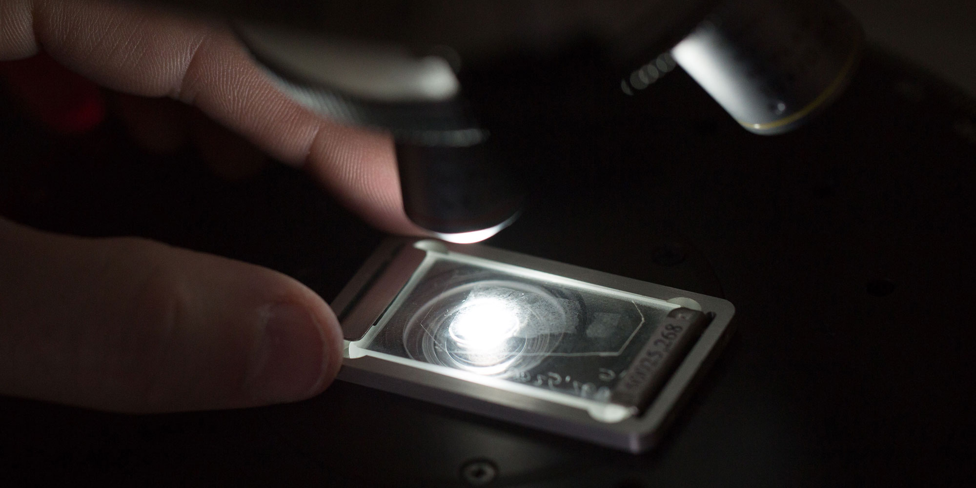 Moon rock being examined under microscope with a shining light in the dark