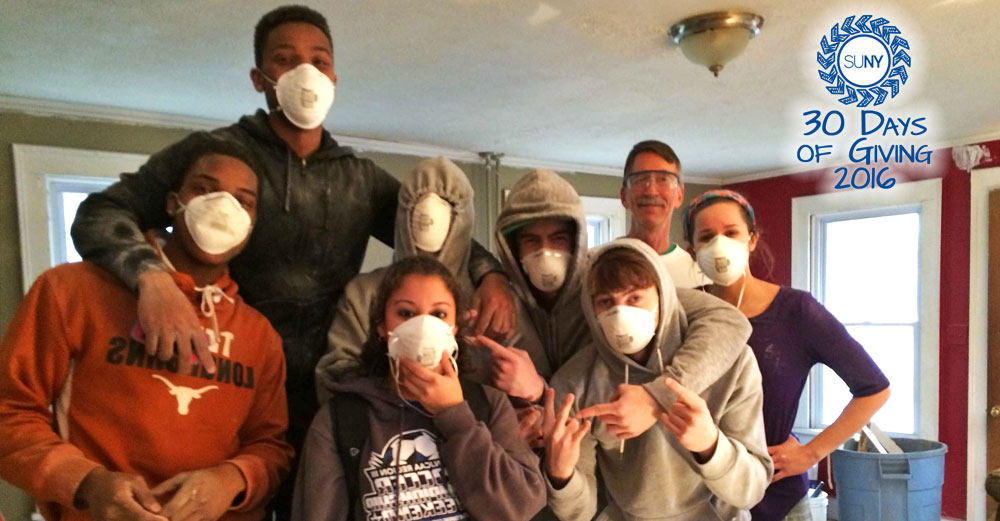 Students from Cayuga Community College pose with their dust masks while building a house for Habitat for Humanity.