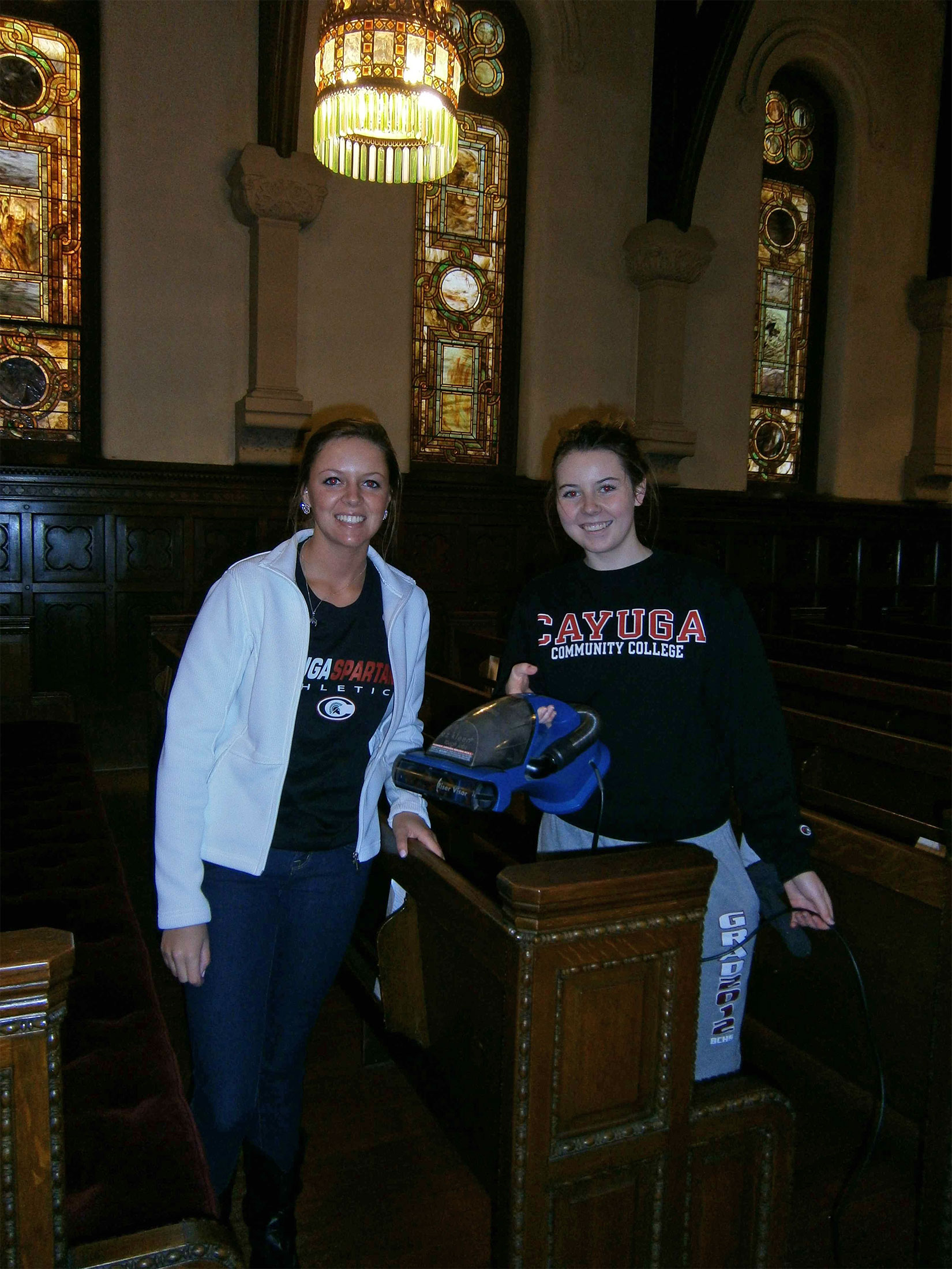 Cayuga Community College volleyball girls shown cleaning a neighborhood chapel.